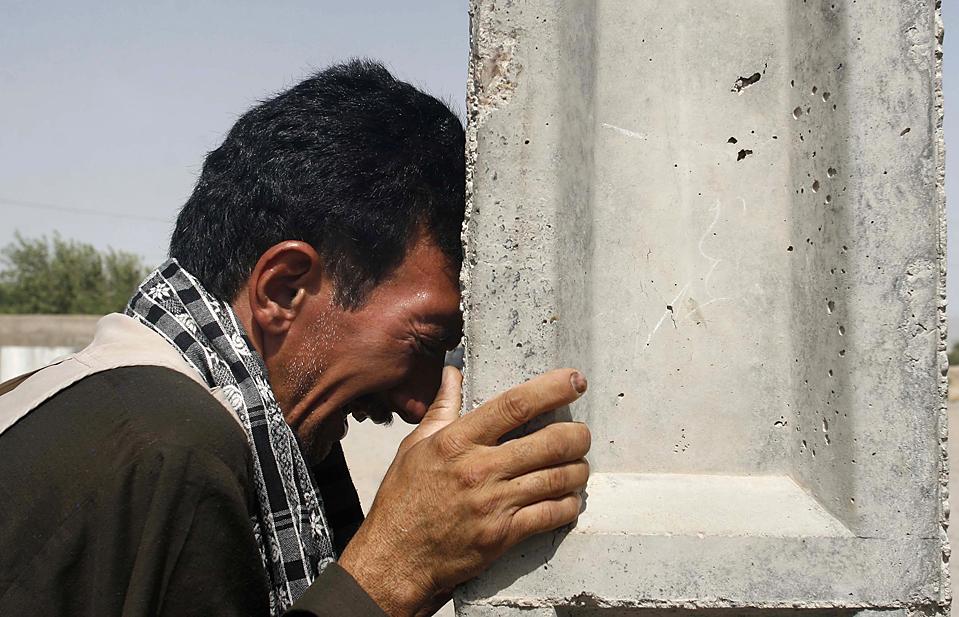 2. Родственник студента Муштабы Мохаммади, которого убили в понедельник осколком бомбы, целившейся в полицейский конвой, скорбит о погибшем, город Герат, Афганистан, вторник. (Fraidoon Pooyaa/Associated Press)