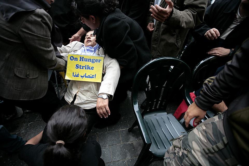 4. Люди помогают иранской протестантке Фарзане Дадкхан, после ее обморока на шестой день голодной забастовки у здания американского посольства в Лондоне во вторник. Демонстранты протестовали против плохого обращения с иранцами, живущими в Ираке. (Shaun Curry/Agence France-Presse/Getty Images)