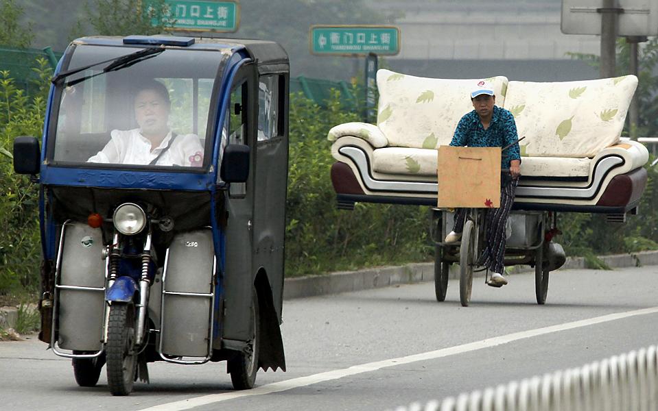 5. Женщина едет на трехколесном велосипеде, нагруженном диваном, по главной дороге в пригороде Пекина во вторник. (David Gray/Reuters)