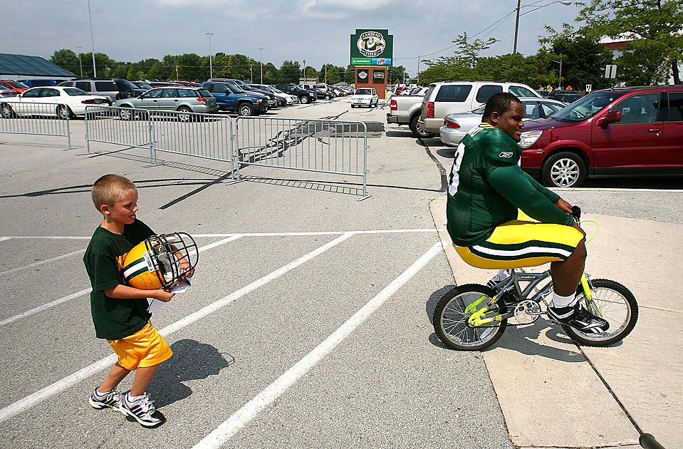 6. Энтони Торибио из команды «Green Bay Packers» на велосипеде по пути на тренировку,  мальчик из летнего тренировочного лагеря несет его шлем, Грин Бэй, штат Висконсин, понедельник. (Jonathan Daniel/Getty Images)