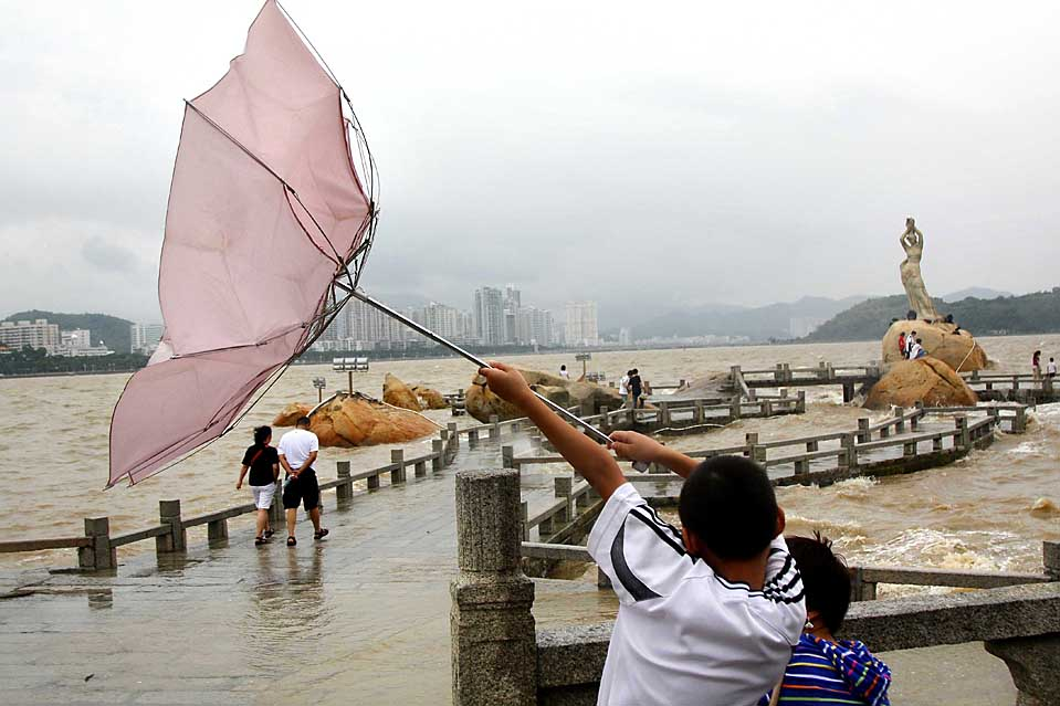 13. Мальчик пытается удержать зонт при сильном порывистом ветре недалеко от города Чжухай, провинция Гуандун, Китай, вторник. К городу приближается тропический шторм «лебедь». (Li Jianshu/Xinhua News via Associated Press)