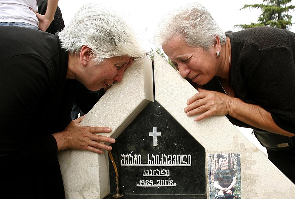2) Родственники плачут над надгробием во время церемонии, которая прошла в Тбилиси в прошлую пятницу. Во время церемонии вспоминали солдат, убитых в прошлогоднем российско-грузнском конфликте в Южной Осетии. В этой короткой войне погибли, по меньшей мере, 390 человек. Около 26 тысяч человек в Грузии все еще живут во временных жилищах. (David Mdzinarishvili/Reuters)