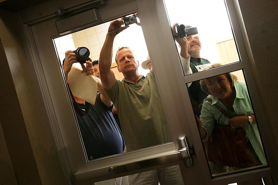 5) Люди фотографируют и снимают видео у переполненного зала, в котором республиканец Джон Д. Динджел, автор реформы законодательства о медицинском страховании, отвечает на вопросы во время совещания в мэрии города Ромулус, штат Мичиган. (Kimberly P. Mitchell/Detroit Free Press via Associated Press)