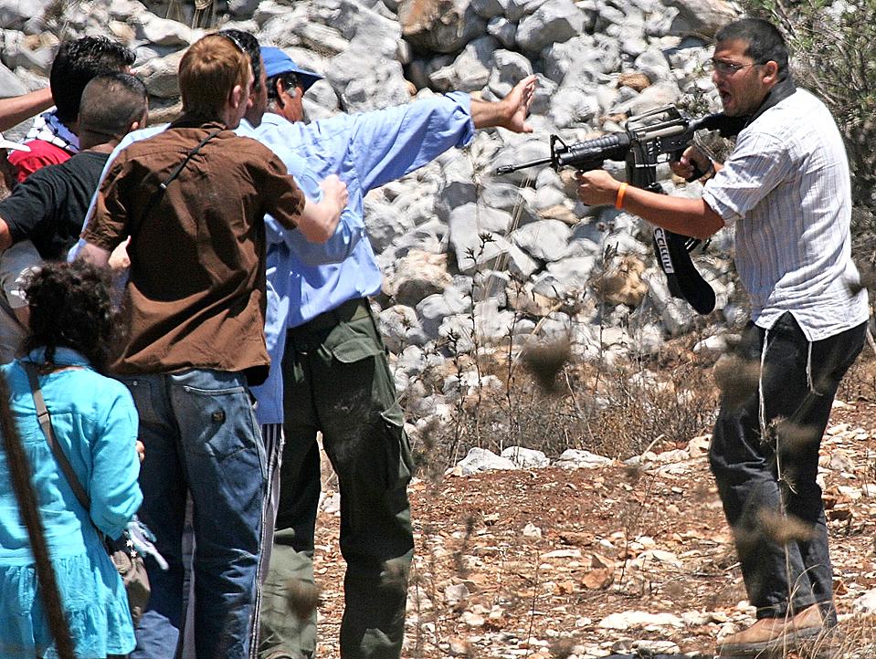 6) Еврейский поселенец направляет автомат на палестинцев и активистов во время демонстрации протеста против конфискации земли у еврейских поселенцев в Бурине на Западном берегу. (Majdi Mohammed/Associated Press)