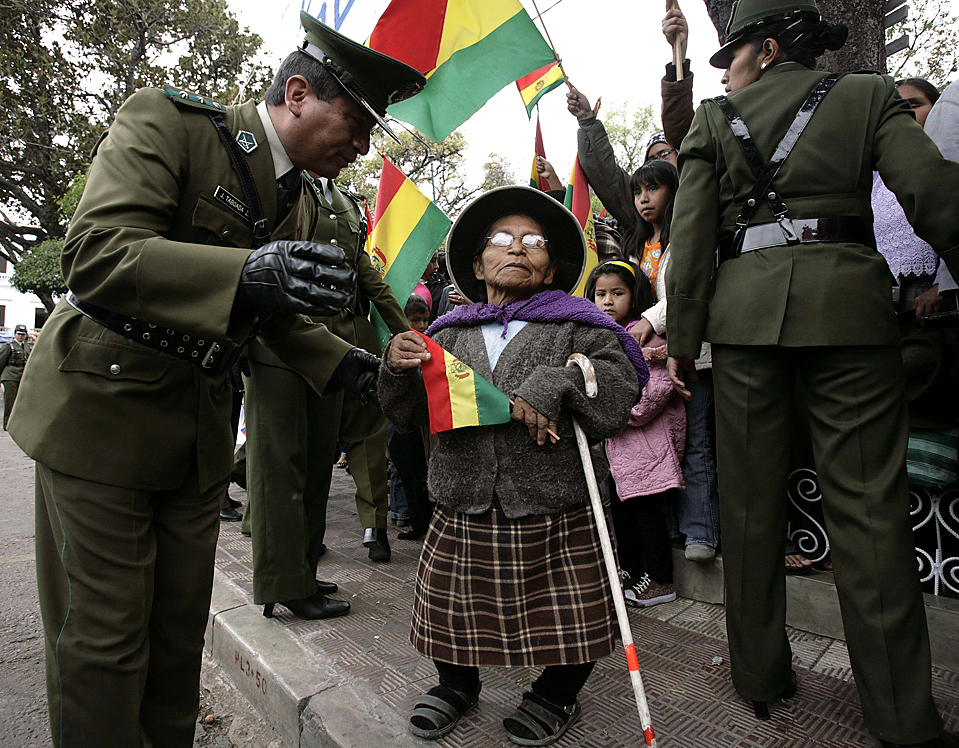 7) Сотрудник полиции помогает стороннице президента Эво Моралеса, во время празднования 184-й годовщины независимости Боливии в боливийском городе Сукре. (David Mercado/Reuters)