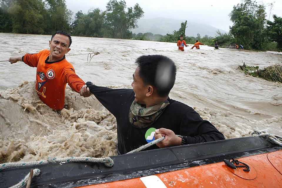 8) Спасатель филиппинской береговой охраны помогает своему коллеге пересечь водный поток в затопленном районе в Ботолане, на Филиппинах. Сильные муссонные дожди вызвали затопления обширных районах на севере Филиппин, вызвав наводнения и оползни, в результате которых погибли, по меньшей мере, 12 человек, включая двух граждан Франции и Бельгии, которые посещали гору Пинатубо (Erik de Castro/Reuters)