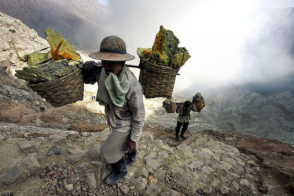 9) Шахтеры несут ведра с серой из кратера вулкана Ijen в Banyuwangi, Индонезия, четверг. Перенося тяжелые грузы и вдыхая ядовитые испарения, эти люди зарабатывают до $ 5 в день. (Irwin Fedriansyah/Associated Press)