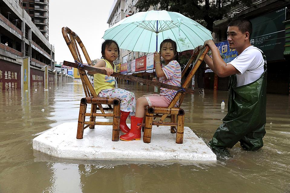 2) Молодой человек толкает самодельный плот, чтобы перевезти двух девочек на другую сторону затопленной улицы в Вэньчжоу, китайская провинция Чжэцзян. Более 1 миллиона человек эвакуированы после того, как тайфун Моракот прошел по материковой части Китая в воскресенье. Также тайфун задел Японию и Тайвань. По меньшей мере, 34 человек погибли, и десятки людей в понедельник были объявлены пропавшими без вести. (Lang Lang/Reuters)