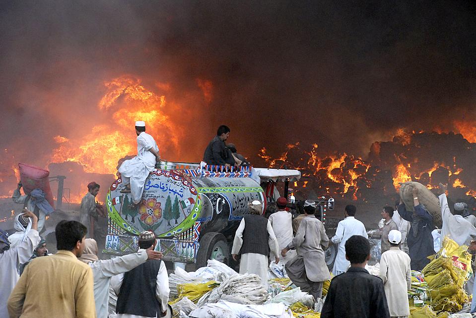 5) Владельцы магазинов пытаются спасти свой товар во время сильного пожара, который вспыхнул на главном рынке пакистанского города Кветте в понедельник. Около 100 магазинов сгорели дотла, четыре человека получили ранения. (Arshad Butt/Associated Press)