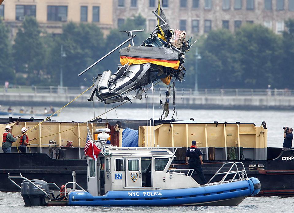 14) Кран поднимает обломки вертолета из реки Гудзон в Нью-Йорке в воскресенье. Должностные лица надеются в понедельник достать самолет из реки после того, как были обнаружены две из девяти жертв столкновение вертолета и самолета в воздухе, которое произошло в субботу. (Seth Wenig/Associated Press)