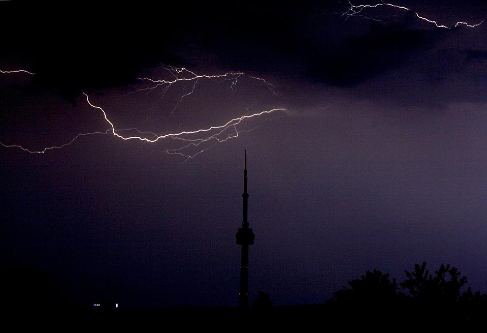 15) Молния в Торонто на фоне «CN Tower», башни используемой для наблюдения и связи. (Darren Calabrese/The Canadian Press via Associated Press)