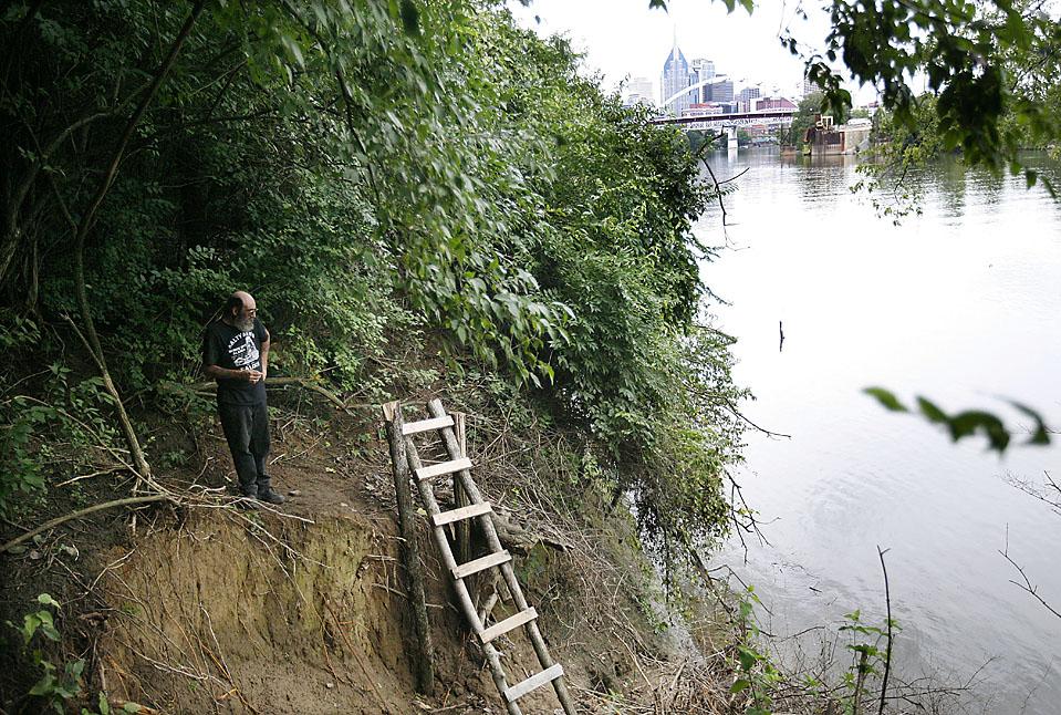 1) Дэвид Уидмер стоит на берегу реки Камберленд на фоне делового центра Нашвилла в Тент Сити в среду. Лестница ведет к участку, с которого жители поселения «бездомных» спускаются к реке, чтобы поплавать. (Josh Anderson for The Wall Street Journal)