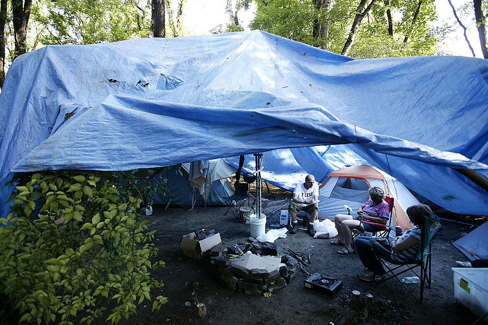 2) Дэвид Олсон курит со своей семьей сигареты ранним утром в палатке Тент Сити в Нашвилле. (Josh Anderson for The Wall Street Journal)