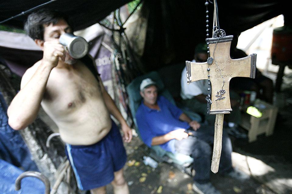 6) Говард Парди (слева) и Рассел Смит пьют кофе у креста с надписью «Ищите добро в каждом» в Тент Сити. (Josh Anderson for The Wall Street Journal)