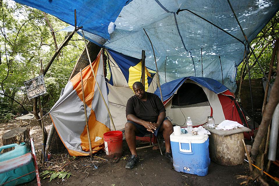 11) 39-летний Лоусон Мотте курит и пьет кофе в своей палатке в Тент Сити. Он живет здесь с начала 2009 года. (Josh Anderson for The Wall Street Journal)