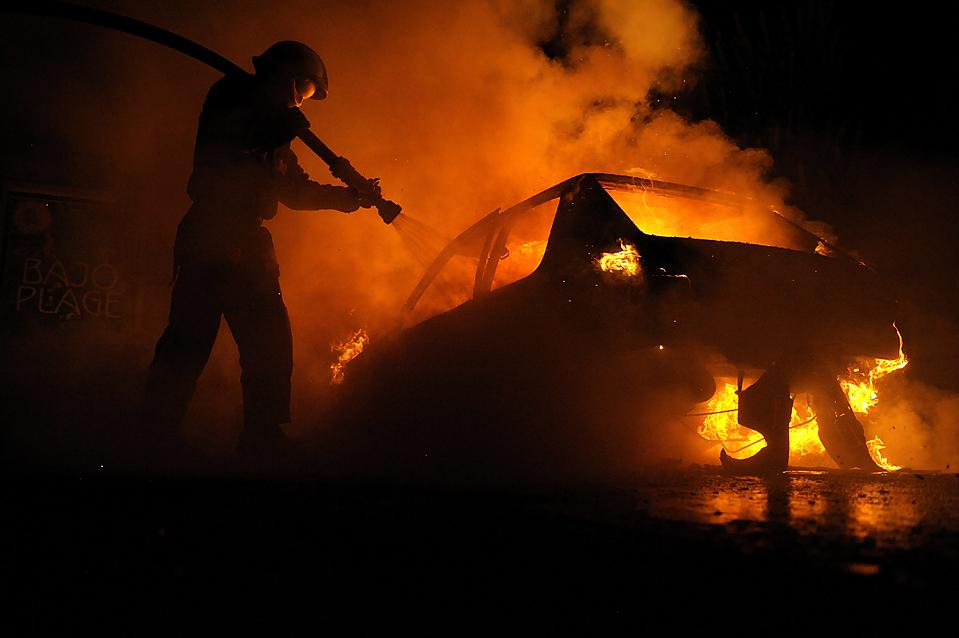 1) Французский пожарный гасит горящую машину после столкновений между молодежью и полицией во французском городе Баньоле (Bagnolet) в понедельник. Молодые люди поджигали автомобили на вторую ночь беспорядков после того, как 18-летний доставщик пиццы погиб в аварии на своем мотоцикле спасаясь от преследующих его полицейских. (Olivier Labanmattei/Agence France-Presse/Getty Images)