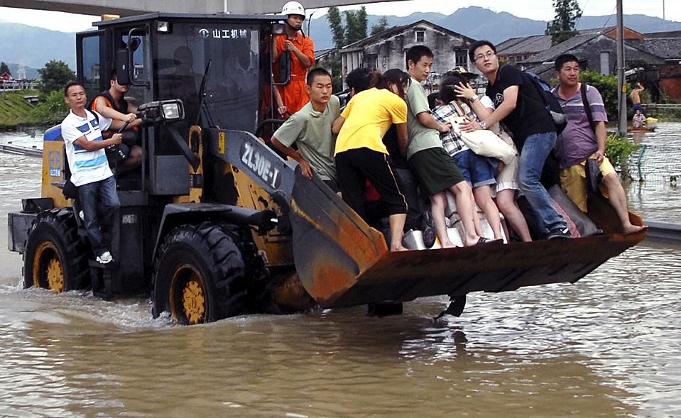 2) Местные жители едут на бульдозере через затопленный район в уезде Cangnan, китайская провинция Чжэцзян. Массивный оползень, вызванный тайфуном Моракот, стал причиной обрушения зданий. По меньшей мере, 22 человека погибли во время оползней и наводнений в Китае и Японии. (Associated Press)