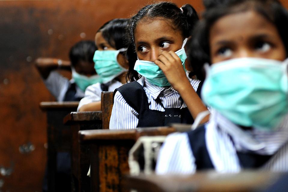 4) Индийские школьники в защитных масках, которые распространяет группа Шив Сена для проведения информационной кампании о гриппе A/H1N1 в Мумбаи. Всемирная организация здравоохранения сообщает, что 1462 человека умерли от этого штамма гриппа в азиатских странах. (Pal Pillai/Agence France-Presse/Getty Images)