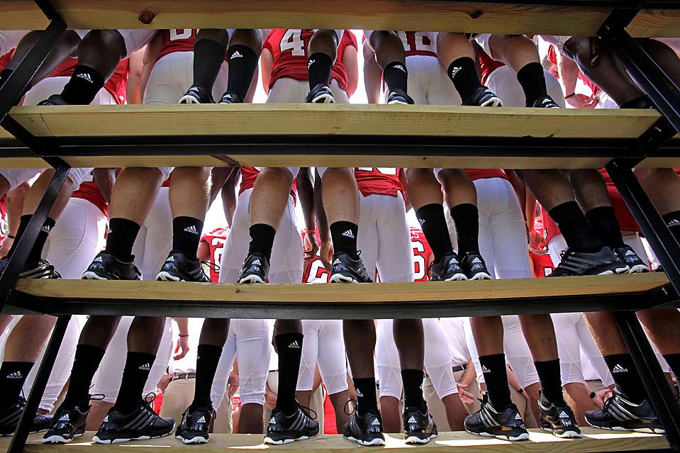 10) Футболисты из команды Университета штата Северная Каролина выстроились для того, чтобы сняться на групповую фотографию для прессы в Роли, штат Северная Каролина. (Gerry Broome/Associated Press)