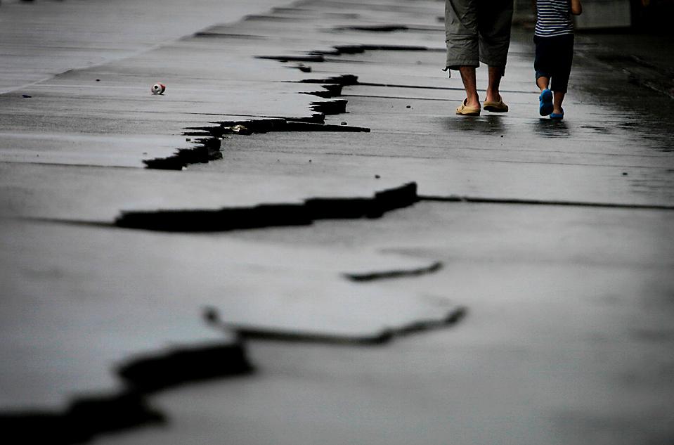 14) Отец с сыном идут по дороге, потрескавшейся после землетрясения силой в 6,5 баллов. Снимок сделан в Японии во вторник. Из-за землетрясения были остановлены поезда и отключены два ядерных реактора для испытаний на безопасность. По меньшей мере, один человек погиб, и более 100 получили ранения. (Itsuo Inouye/Associated Press)