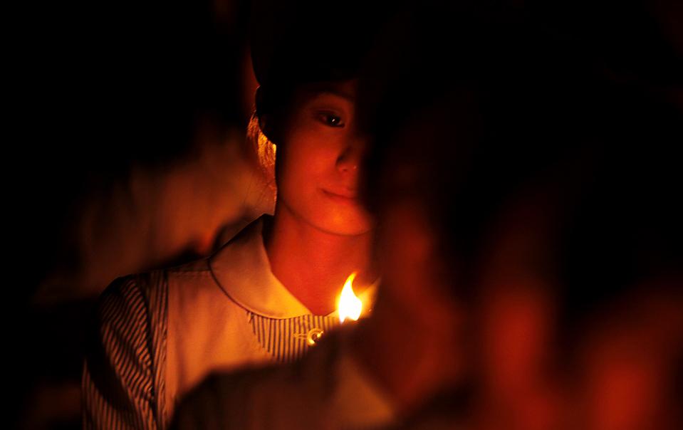 1) Студентки-медсестры Красного Креста идут с зажженными свечами в память о Флоренс Найтингейл во время вручения медали медсестре Токико Саита в Токио. (Junji Kurokawa/Associated Press)