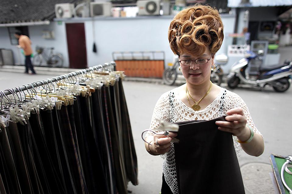 3) 47-летняя владелица магазина Чжэнь Гун Чуй поправляет брюки в своем магазине в Шанхае. По данным министерства финансов, общенациональные налоговые поступления в Китае увеличилась в июле на 10,2% по сравнению с показателями годом ранее. (Nir Elias/Reuters)