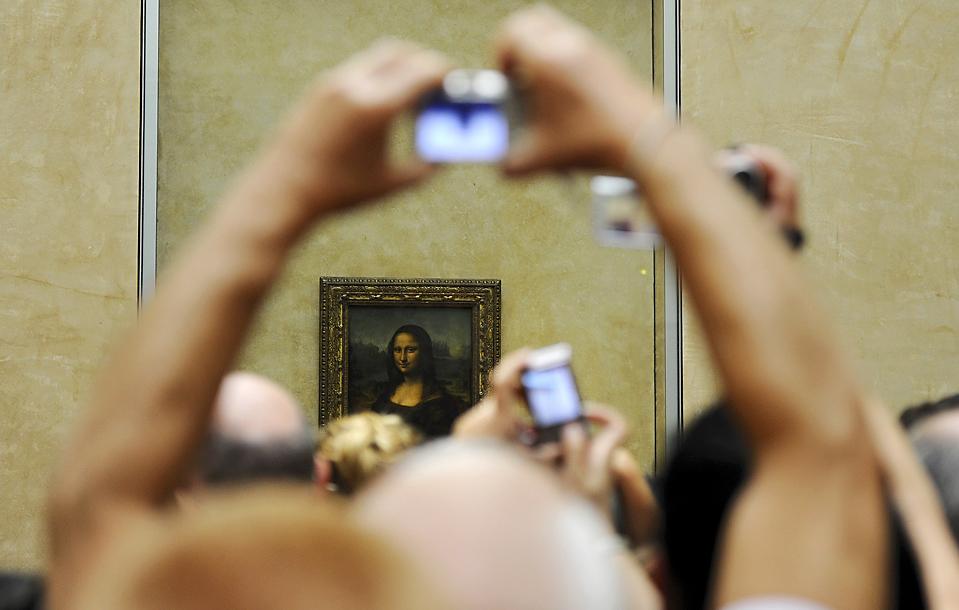 """9) Туристы фотографируют знаменитое полотно иальянского живописца Леонардо да Винчи """"Мона Лиза"""" в Лувре в Париже. 2 августа россиянка разочарованная неудавшимися попытками получить французское гражданство бросила в картину керамическую чашку, но как сообщает  пресс-секретарь музея, не повредила ее. Картина защищена пуленепробиваемым стеклом. (Jacky Naegelen/Reuters)"""