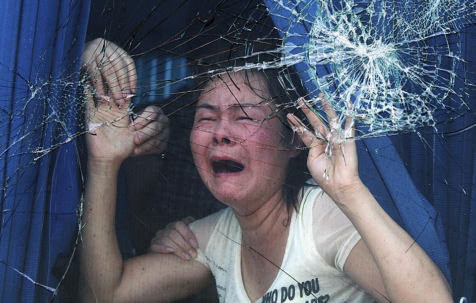 2) Женщина кричит о помощи за разбитыми стеклами туристического автобуса в Ху Каунти, провинция Шаанкси, Китай, среда. Туристы застряли в автобусе на восемь часов после столкновения со скутером, в результате которого погибло два человека. Родственники жертв атаковали автобус, пока власти не вступили в переговоры об освобождении туристов. (Associated Press)