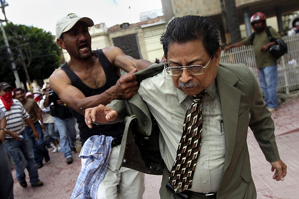 3) Сторонник свергнутого президента Гондураса Мануэля Зелайи схватил Рамона Веласкеса, вице-президента Конгресса, во время протеста за стенами здания Национального Конгресса в Тегусигальпе, Гондурас, среда. Военные выгнали мистера Зелайю в июне после того, как Высший Суд выдал ордер на его арест. (Edgard Garrido/Reuters)