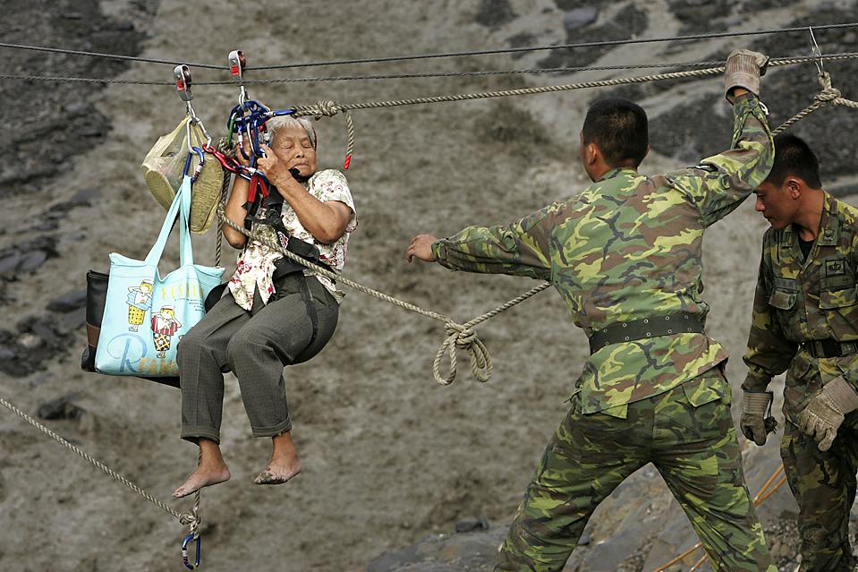 16) Солдаты спасают женщину с помощью троса над рекой Ба Си Лан в Синфе, Тайвань, четверг. Наводнения, вызванные тайфуном Моракот, стали причиной гибели дюжин ее знакомых и оставили тысячи других без крова. (Wally Santana/Associated Press)