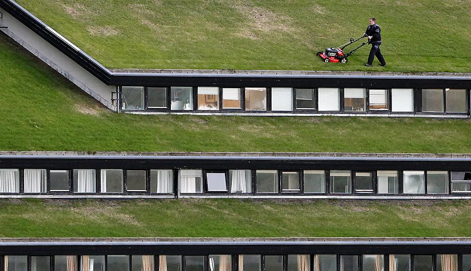 12) Рабочий стрижет газон на крыше правительственного здания недалеко от Торсхавна, столицы Фарерских островов, четверг. (Bob Strong/Reuters)
