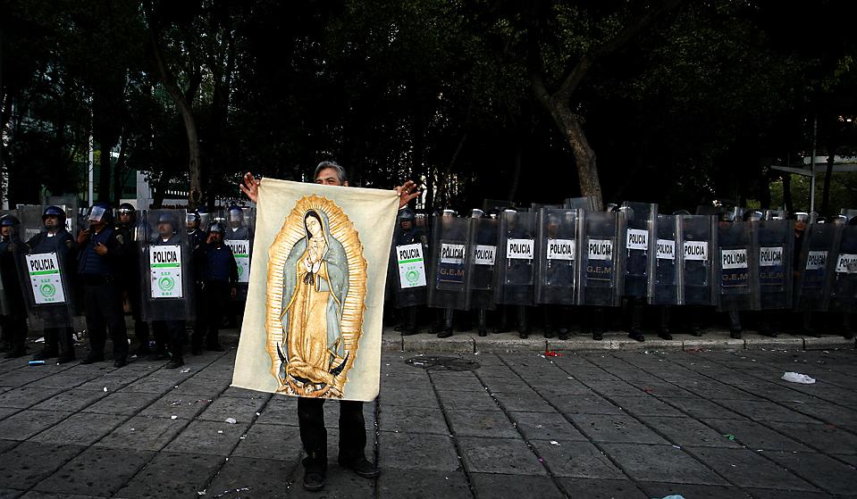 13) Мужчина держит образ Девы Марии Гваделупской перед отрядом полиции во время празднования футбольных фанатов Мексики победы сборной в квалификационном матче против США со счетом 2:1, Мехико Сити, среда. (Marco Ugarte/Associated Press)
