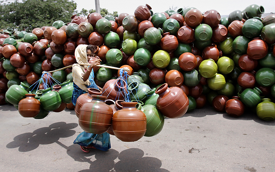 14) Женщина собрала пластиковые контейнеры для сбора воды в Хайдарабаде, Индия, четверг. Уровни подземных вод в Индии упали на 20% больше, чем ожидалось, из-за чрезмерного водоотлива, грозящего перерасти в серьезный дефицит пищи и воды, - показало исследование космического агентства США. (Mahesh Kumar A./Associated Press)