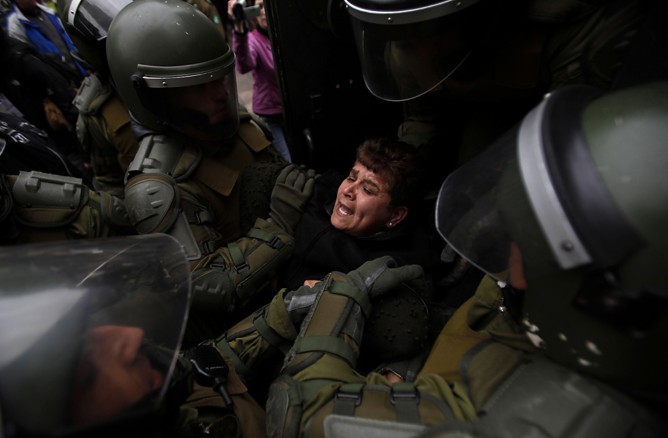 2) Полиция задержала женщину, которая протестовала от имени индейцев мапуче в Сантьяго, Чили. Мапуче пообещали захватить землю после того, как один из активистов был смертельно ранен полицейскими. Власти говорят, что была самооборона. (Roberto Candia/Associated Press)