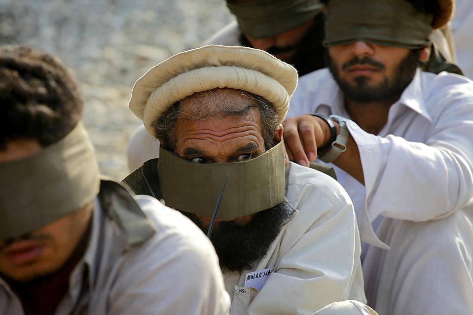 """4) Человек выглядывает из-за повязки на глазах, сидя рядом с другими людьми, которые подозреваются в причастности к движению """"Талибан"""" после ареста американскими силами в афганской провинции Кунар в пятницу. В четверг, пакистанские вертолеты атаковали базы движения """"Талибан"""", в результате чего погибли 11 боевиков.  Давление продолжается после того как было, сообщено о смерти лидера пакистанского движения """"Талибан"""" от ракетного удара США на позапрошлой неделе. (Carlos Barria/Reuters)"""