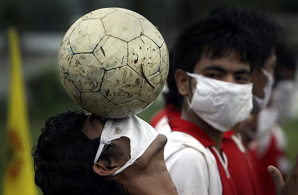 5) Индийский футболист с мячом во время турнира недалеко от индийского города Гаухати. На футболистах маски для профилактики гриппа A/H1N1. По меньшей мере, 20 человек умерли от этого штамма гриппа в Индии. (Anupam Nath/Associated Press)