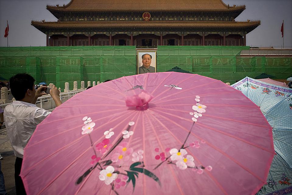 6) Туристы с зонтиками возле ворот Тяньаньмэнь, которые сейчас ремонтируют перед празднованием 60-й годовщины со дня основания Народной Республики Китай. Снимок сделан в Пекине в пятницу. (Alexander F. Yuan/Associated Press)