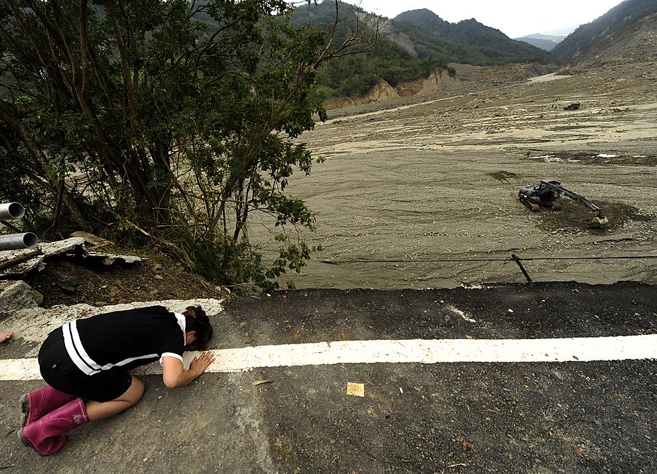10) Женщина оплакивает своих родственников пропавших без вести в тайваньском городе Hsiaolin после тайфуна Моракот. Президент Ма Ин-цзю озвучил общее число погибших - более 500 человек. При этом в адрес правительства все чаще звучит критика, поскольку правительство не достаточно быстро эвакуировало население. (Peter Parks/Agence France-Presse/Getty Images)