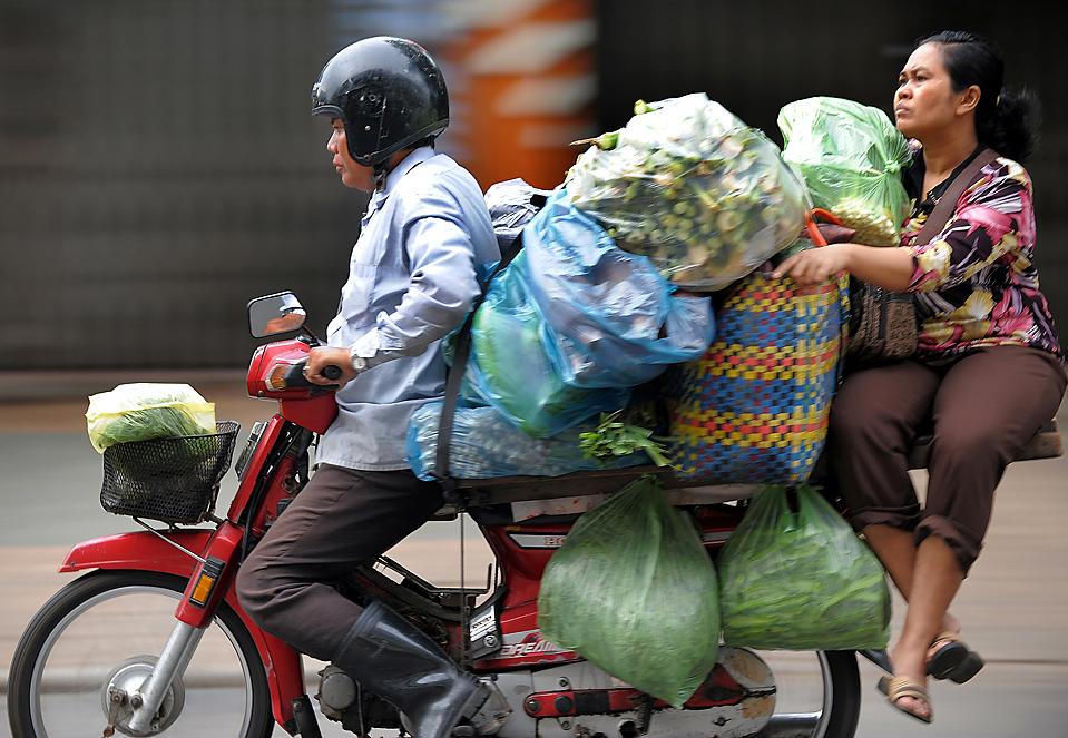 13) Водитель с пассажиром едут на мотоцикле, груженном овощами, вдоль улицы в камбоджийском городе Пномпень. (Tang Chhin Sothy/Agence France-Presse/Getty Images)