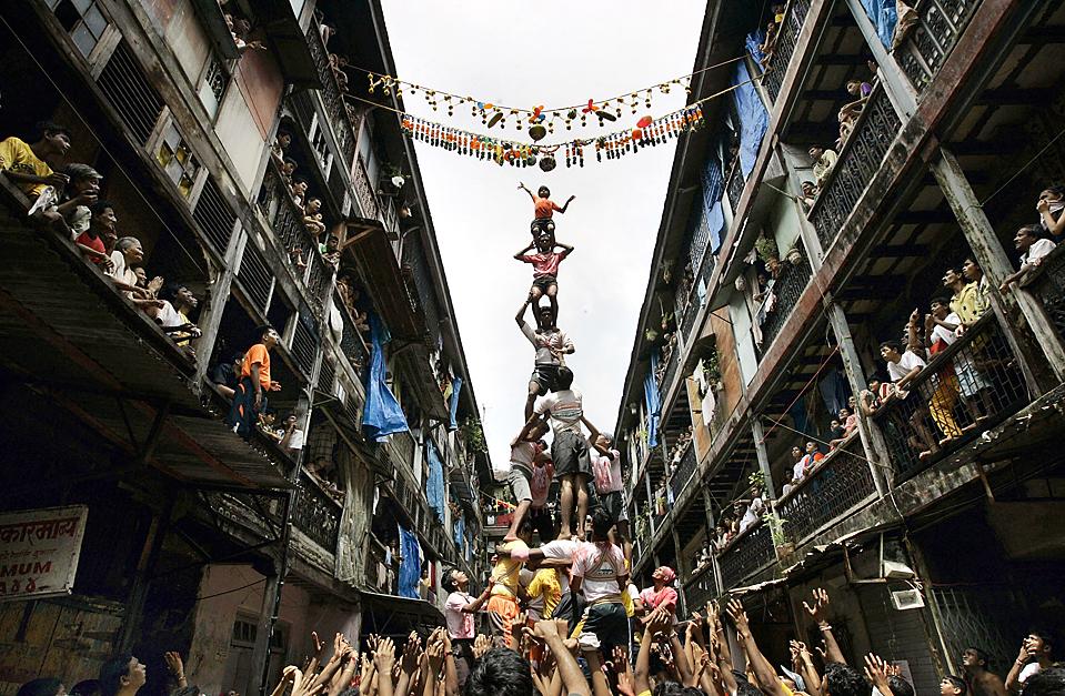 """14) Люди образовали пирамиду, чтобы достать сосуд с маслом во время празднования """"Janmashtami"""", дня рождения индуистского Бога Кришны в Мумбаи в пятницу. (Rajanish Kakade/Associated Press)"""