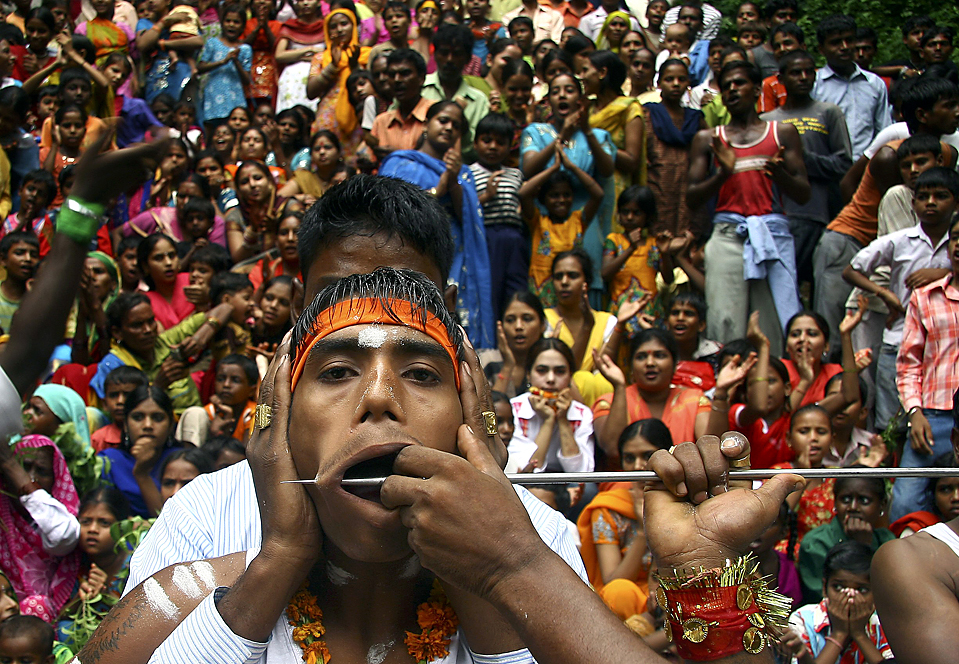 """15) Человек пронзает щеку во время ежегодного индуистского религиозного шествия под названием """" Шитала Мата"""" в индийском городе Чандигархе, в воскресенье. С помощью этих болезненных ритуалов люди демонстрируют свое покаяние и преданность Богине Шитале. (Ajay Verma/Reuters)"""