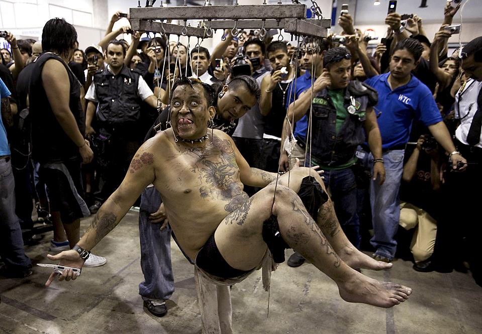 6) Художник Хорхе Кастро, специализирующийся на татуировках, свисает с потолка на крюках и веревках, подвешенный за пирсинг во время выставки Тату Экспо в Мехико. (Jorge Dan Lopez/Reuters)