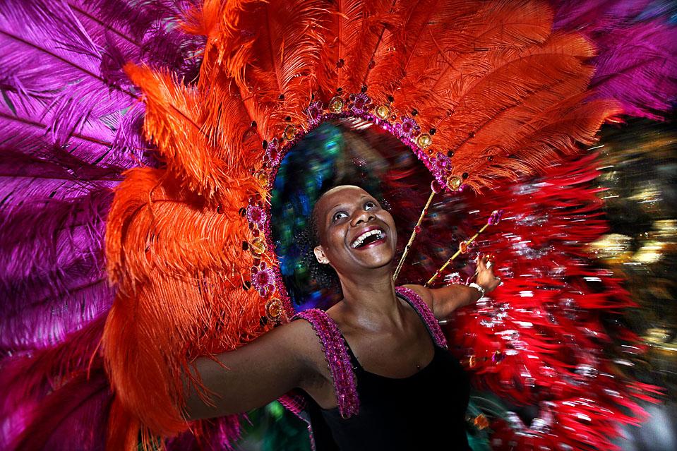 5) Участница ежегодного карнавала «Bachanal Mas», который пройдет в Ноттинг Хилл в Лондоне в эту субботу, примеряет часть уже готового карнавального костюма. Добровольцы изготовили около 350 костюмов из самых разнообразных материалов: от перьев до стекловолокна и стали. (Dan Kitwood/Getty Images)
