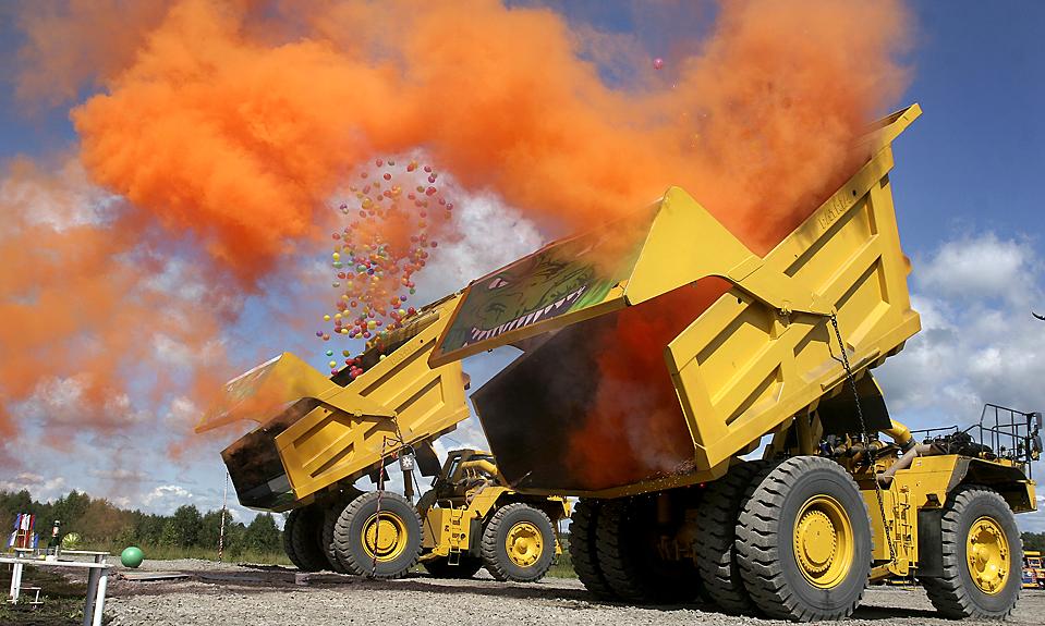 3) Желтые самосвалы сгружают воздушные шары и заряд оранжевого дыма во время шоу тяжелой техники в сербском городе Кемерово. (Yury Yuriev/Agence France-Presse/Getty Images)