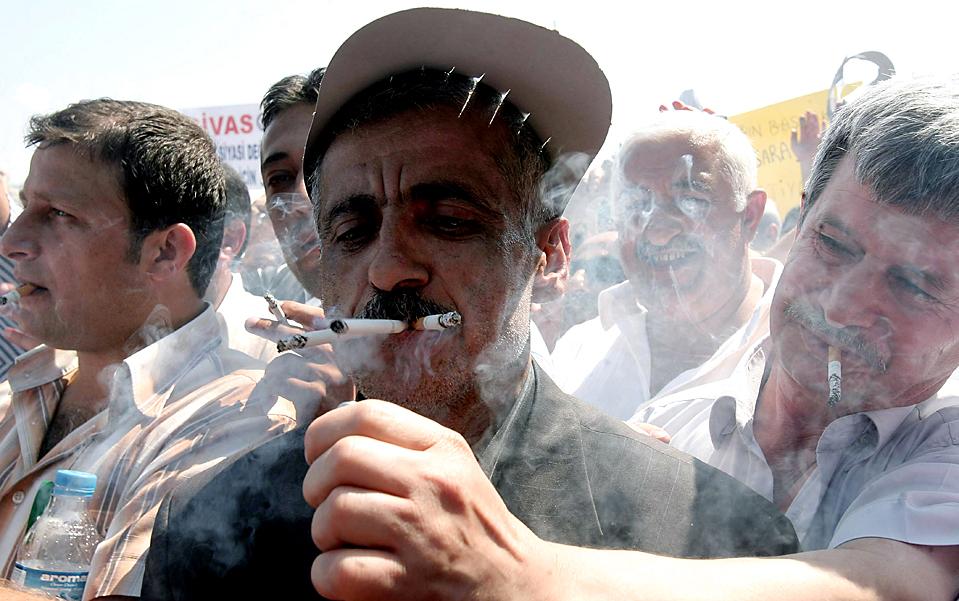 3) Владелец кафе курит сразу несколько сигарет во время акции протеста в Анкаре, Турция. Демонстранты выступали против запрета правительства на курение в помещении. Этот общенациональный запрет распространяется также на бары и рестораны. (Adem Altan/Agence France-Presse/Getty Images)