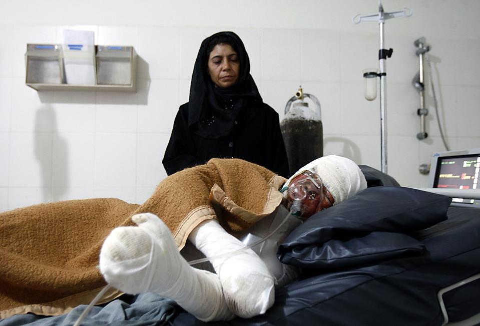 16) Мать смотрит на свою дочь в больнице афганского города Герата. Мать говорит, что ее дочь, которую два года назад вынудили выйти замуж за 70-летнего мужчину, пыталась совершить самосожжение, после того, как люди узнали о ее романе с более молодым мужчиной. (Raheb Homavandi/Reuters)