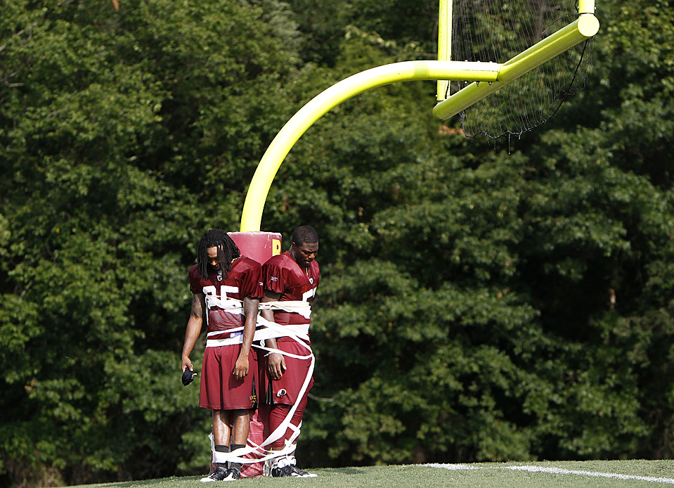 13) Крайний защитник из команды «Washington Redskins» Кевин Барнс, слева и полузащитник Роберт Хенсон, привязанные к баскетбольной вышке после тренировки команды в тренировочном лагере в Эшберн, штат Вирджиния. (Pablo Martinez Monsivais/Associated Press)