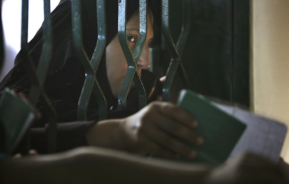 12) Палестинская женщина ждет разрешение на получение пайка от Ближневосточного агентства Организации Объединённых Наций для помощи палестинским беженцам и организации работ на складе агентства в лагере беженцев города Газа. БАПОР обратились с призывом о предоставлении 181 млн. долл. США для обеспечения бедных слоев населения в секторе Газа продовольствием, рабочими местами и денежной помощи. (Tara Todras-Whitehill/Associated Press)
