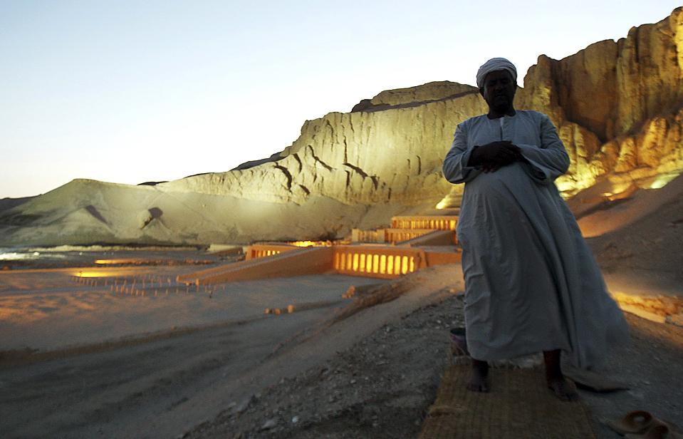 8) 52-летний Юсеф Абд Эль-Райхем, молится на открытии храма египетской королевы Хатшепсут в Луксоре (на фоне). Это – восстановленный древний храм. Правление Хатшепсут было самым длительным из всех царствований женщин-фараонов. Эль-Райхем работал на этом строительстве 31 год. (Amr Abdallah Dalsh/Reuters)