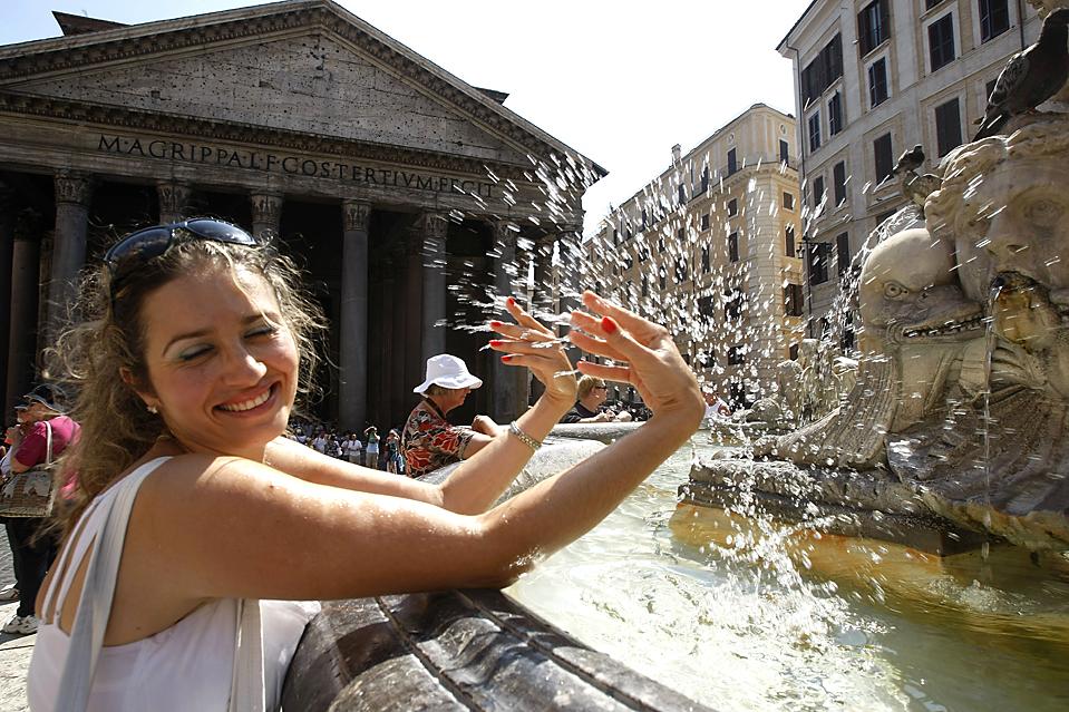 7) Женщина освежается водой из фонтана в Риме. В ближайшие дни во многих городах Италии будет сохраняться знойная погода. (Pier Paolo Cito/Associated Press)